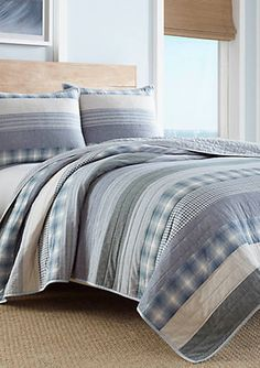 Horizontal bands of chambray blues and ivory are pieced with a classic plaid and stripe to create this casual quilt with a soft, sun-bleached quality. Channel quilting follows the horizontal orientation and ivory binding adds a crisp finish. Full/Queen quilt measures: 90-in. x 90-in.