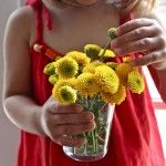 child with vase of yellow flowers. Luscious flowers. Live a luscious life with LUSCIOUS: www.myLusciousLife.com