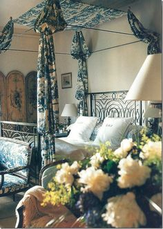 This bedroom has a beautiful blue and white toile draped iron bed and antique screen.