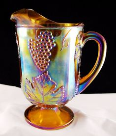 Indiana Glass Harvest grape marigold carnival large water pitcher.  The water pitcher has a beautiful golden iridescent with gorgeous hues of purples, and teals.  The vintage Harvest pitcher has a scalloped edging around the upper rim and sits on a pedastal base with beading around the short stem.  The 70 oz pitcher stands about 10 1/2 inches tall.  $40.00