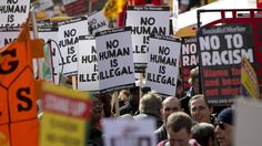 People hold placards during a Stand up to Racism and Fascism rally in central London March 22, 2014. REUTERS/Neil Hall (BRITAIN - Tags: SOCIETY CIVIL UNREST) - RTR3I5K2