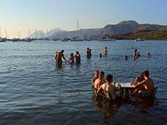 Isola di Vulcano - In primo piano bagnanti e imbarcazioni nella baia delle Sabbie Nere, in secondo e terzo piano le isole di Lipari e Salina | da Lorenzo Sturiale