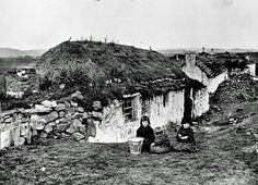 Three children sitting outside a cottage in Stornoway in the 1890s