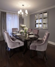 Dining Room With Wall Mirror Chandelier Dark Wood Table And Purple Tufted Chairs