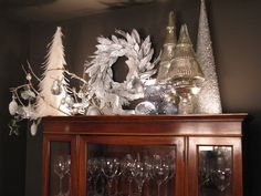Christmas decorating above china cabinet in dining room. This display creates a snowy, winter scene, using a silver wreath and various white, glass and silver xmas objects and back lighting.