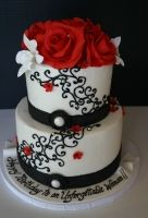 Two tier buttercream cake with icing scrollwork, sugar flowers and orchids