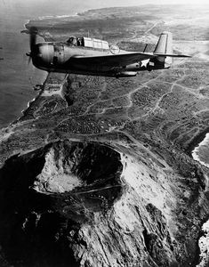 TBM-3 Avenger flying over Mount Suribachi on Iwo Jima after US forces had fully occupied the island March-April 1945. Note storage tanks tents and other improvements set up by US forces.