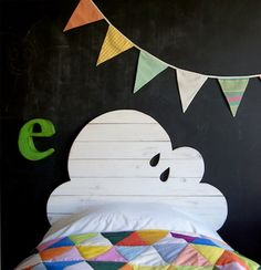 Cloud headboard, blackboard wall and bright bunting. Just need a jigsaw and some paint to make that headboard. Way cool!