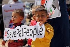 """GAZA CITY, GAZA- Palestinian activists take part in a rally titled """"Save Pal People"""" against the Israeli occupation and Gaza blockade in front of a tower which was destroyed during the 50-day war between Israel and Hamas in the summer of 2014."""
