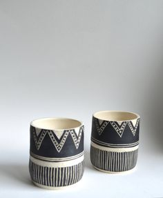 These tumblers are wheel thrown, painted with a black velvet underglaze, and include hand carved designs. Inside of tumblers are glazed with a matte clear Ceramic Cafe, Ceramic Mugs, Stoneware, Sgraffito, Pottery Painting, Ceramic Painting, Slab Pottery, Ceramic Pottery, Cerámica Ideas