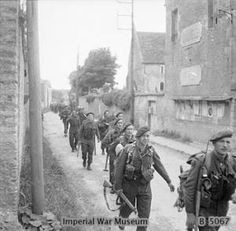 Royal Marine Commandos attached to Division for the assault on Sword Beach move through Colleville-sur-Orne on their way to relieve forces at Pegasus Bridge, Normandy, 6 June 1944 Military Photos, Military History, Ww2 History, British History, D Day Normandy, Normandy France, Normandy Ww2, British Commandos, Marine Commandos