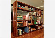 Perfeita para dividir os ambientes na sala, a estante é totalmente vazada nos fundos. Apenas apoiada no piso, fica bem se encostada na parede em outros cômodos. A peça é de ripas de madeira encaixadas, sem parafusos. Projeto de Juliana Llussá