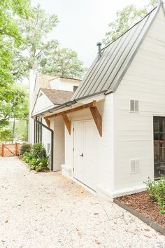 White exterior, black window panes, gray metal roof, wood beams.