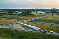 An image of the world's largest wind turbine blade being transported down a highway. The perspect of the photo shows the massive scale of the blade compared to vehicles.