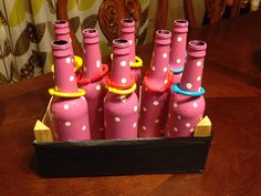 Minnie Mouse Game Ring Toss with Beer Bottles painted pink with white polka dots. Used baby teething rings.