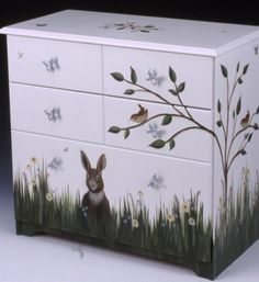 dresser with painting of bunny in grass, with a bird in the nearby tree