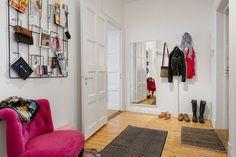 druciany wieszak na drobne akcesoria, na ścianie,różowy fotelik,szary dywanik,biały wieszak drzewko i duże biale lustro na ścianie w przedpokoju z drewnianą podłogą