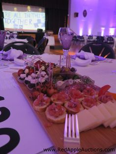 Not all centerpieces need to be flowers. At this Italian-themed auction fundraiser, the centerpiece was the yummy starter course of olives, cheeses, etc.  #FoodCenterpieces