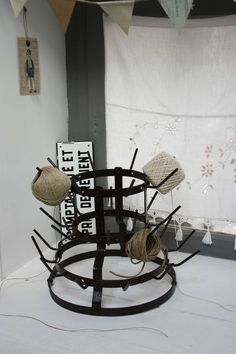 Use a bottle drying rack to organize twine and ribbon on a craft table! Love this idea!