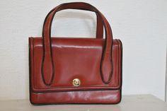 Wunderschöne Handtasche in Minikofferoptik. Aus den 60er Jahren, aus feinem orangebraunem Leder mit zwei kleinen Taschengriffen. Innen aufgeteilt in 4 Fächer. Die Tasche schließt  mit einer...