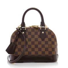 This Louis Vuitton Alma BB is a miniature version of the iconic Alma design. It is made from Damier Ebene canvas with dark brown leather trim and golden brass hardware. Details include a detachable strap, double-zip closure, and fully lined interior with one open pocket. Carry this style hand-held, on the forearm, over the shoulder, or cross body.