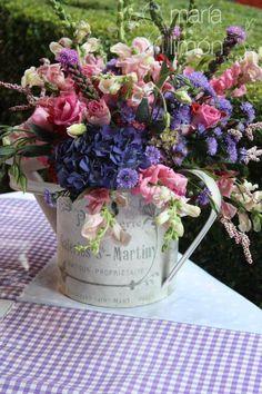 Centro de mesa en base decorativa en tono rosa y morado.