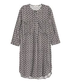 Straight-cut dress in a viscose weave with a round neck, concealed button placket, chest pockets, 3/4-length sleeves and slits in the sides. Unlined.