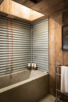 The bathroom features corrugated tin walls and a custom-built concrete bath and countertop. The space is illuminated by a skylight and is closed off for privacy by a sliding steel barn door. Galvanized Shower, Bathroom Inspiration, Luxury Cottage, Bathrooms Remodel, Industrial Bathroom, Rustic Bathroom Designs, Concrete Bath, Modern Bathroom Remodel, Bathroom Design