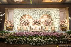 Love this stage decor in white n purple flowers | White floral wall with french windows as backdrop | French settee sofas | Floral installations |  Reception decor ideas | Credits: lightworksjakarta.com | Every Indian bride's Fav. Wedding E-magazine to read. Here for any marriage advice you need | www.wittyvows.com shares things no one tells brides, covers real weddings, ideas, inspirations, design trends and the right vendors, candid photographers etc.