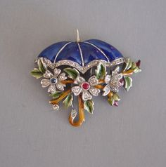 """DUJAY unsigned umbrella fur clip with a blue enameled umbrella, brown and green handle and leaves, and rhinestones in clear, red and blue set in silver tone metal, 1-3/4"""" by 1-1/3"""""""