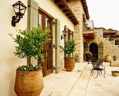 elevation, stone on walls, corbels, shutters, terra-cotta pots, roof tiles, coach lights, doors, wood under balcony, rough hewn floor!!!