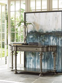 A versatile piece, this display table is equally handy in the living room or dining room, against a sofa or against the wall. This subtly traditional yet breezily casual piece features tall, turned wood legs and an open shelf for storing serving platters or a beachy-themed decorative display.