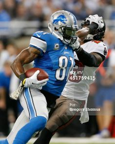 Calvin Johnson of the Detroit Lions stiff arms Mark Barron of the Tampa Bay Buccaneers after a second quarter catch at Ford Field on November 2013 in Detroit, Michigan. Detroit Lions Football, Detroit Sports, Nfl Football, Football Players, Football Helmets, Brandon Marshall, Ford Field, Calvin Johnson, American Football