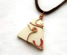 Surfing pendant features Irish sea pottery wire wrapped in solid copper wire and hung on a russet brown, cotton, crochet necklace. Ocean-buffed pottery that washes up on Dublin shores most often dates back to the Victorian era. This triangular specimen was the perfect shape for a pendant and its milky surface was crying out for a little wire art. It carries a hint of its original red pattern which appears to be a leaf. Though the leaf is a small feature on the piece, it conveys a sense of…