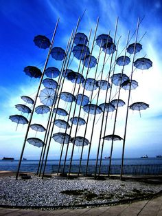 "Greece, The ""Umbrellas"" sculpture on Thessaloniki's seafront is a high artistic creation created by Georgios Zoggolopoulos. Blue Umbrella, Umbrella Art, Land Art, Singing In The Rain, Environmental Art, Outdoor Art, Public Art, Oeuvre D'art, Installation Art"