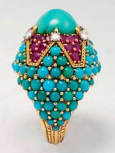 Magnificent Marchak Paris Turquoise and Ruby bombe Ring.  18 karat yellow gold ring, centering one oval cabochon cut turquoise, six round brilliant cut diamonds, and 36 mixed- cut rubies, and numerous round cabochon turquoise. Hand inscribed MARCHAK PARIS 33396.