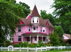"""This is an extremely attractive Victorian house - except for the color. What a great disservice to paint it candy pink and fuschia. Even the white """"trim"""" is done incompletely. What a nice porch, turret, 2nd floor balcony, and gables, fence and yard."""