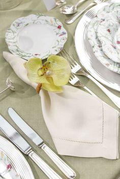 Guardanapo em linho e porta-guardanapo no modelo Orquídea Verde, ambos da nossa marca Couvert, usados para compor uma mesa de almoço no jardim.