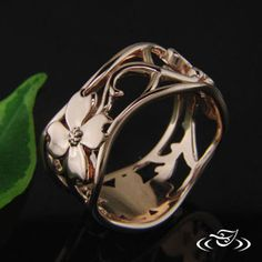 Custom 14kt rose gold band with pierced vine and dogwood flower design wedding band with small bud details on branches. Engraved vein detail on leaf in a high polish finish.