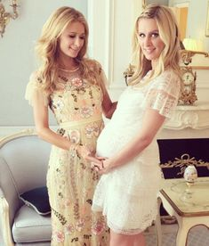 Wearing a white lace dress that highlighted her bump, Nicky, 32, (right) was joined by her sister, Paris