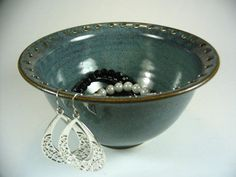 Cool idea of a jewelry bowl.  Holes in the lip for earings as well as the bowl for other items. Cool affect of the brown edge.