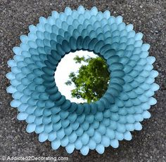 Plastic Spoon Chrysanthemum Mirror: Break up plastic spoons and stick them on a cardboard wreath form you can get from a crafts store. Paint them with a color you like, and stick a mirror in the center. Find more detailed instructions here.   Source: Addicted2Decorating