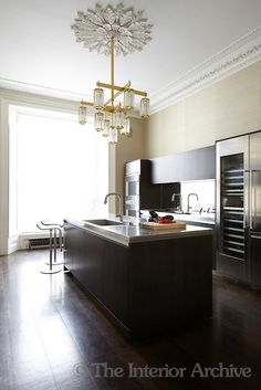 The kitchen is a contrast of periods, fitted with contemporary cabinets by Boffi yet retaining its Victorian mouldings and ceiling rose ~ Peter Mikic, London