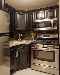 Dark wood kitchen cabinets and stainless steel appliances, corner kitchen design