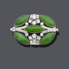 An art deco jade and diamond brooch, circa 1930  The oval pierced plaque of geometric design set with old brilliant, single and baguette-cut diamonds and marquise-shaped jade cabochons, diamonds approx. 2.00ct. total, length 4.2cm.