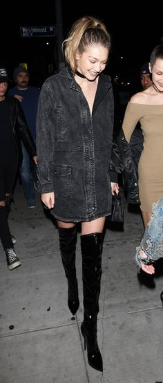 Gigi Hadid wears a black denim shirtdress, black over-the-knee boots, and a black choker.
