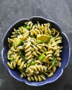 Quick and easy pasta with pesto, spinach, peas, and avocado. So EASY and creamy! On SimplyRecipes.com #pesto #avocado