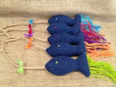 This cat teaser toy features a blue denim fish with a whimsical tail and matching ribbon. This toy is upcycled from blue denim fabric (shades may vary), hemp rope, ribbon, cotton thread, and polyester stuffing. Choose from 5 vibrant colors: Blue, Maroon, Purple, Orange, and Green. Each fish is approximately 4 inches in length (not including tail or string). Upcycled toys are made from unwanted clothing and other fabric items. We wash them thoroughly and turn them into new toys that any pet…