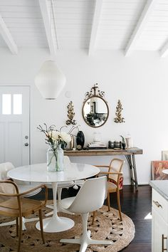 white entryway with gold wall decor and round woven rug. / sfgirlbybay