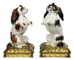 A PAIR OF ORMOLU-MOUNTED CONTINENTAL MODELS OF BOLOGNESE HOUNDS  ONE PROBABLY MEISSEN, POSSIBLY 18TH CENTURY, THE OTHER PROBABLY SAMSON, LATE 19TH CENTURY, THE MOUNTS 19TH CENTURY  Each after the model by J.J. Kaendler standing on hind legs in begging pose, the Meissen example enriched in shades of brown, the Continental porcelain example in black, on ormolu tasselled cushion cast with fleur-de-lys, areas of restoration  11½ in.  high; 8¾ in.  wide; 7 in.  deep; and similar